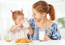 Happy family mother and baby daughter girl at breakfast: biscuit Royalty Free Stock Photos
