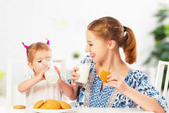 Happy family mother and baby daughter girl at breakfast: biscuit Stock Image