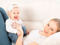 Happy family. Mother and baby daughter at home on the sofa Stock Photos