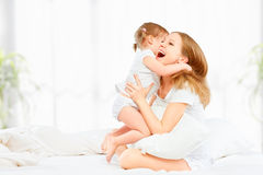 Happy family mother and baby daughter playing and laughing baby Stock Photos
