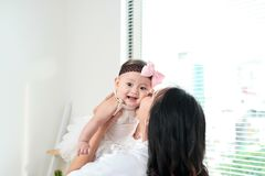 Happy family. Mother and baby daughter plays, hugging, kissing at home near window stock images