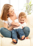 Happy family. Mother and baby daughter on the sofa Stock Photos