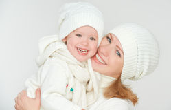 Happy family: mother and baby daughter in white winter hats laughing. On a gray background stock photography
