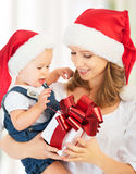 Happy family mother and baby with gift  in Christmas hats. Happy family mother and baby with gift   in red Christmas hats Royalty Free Stock Photos