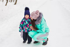Happy family mother and baby girl daughter playing and laughing in winter outdoors in the snow Royalty Free Stock Photos