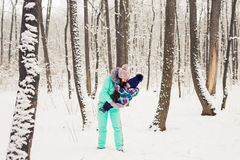Happy family mother and baby girl daughter playing and laughing in winter outdoors in the snow Royalty Free Stock Image