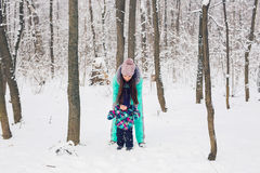 Happy family mother and baby girl daughter playing and laughing in winter outdoors in the snow Stock Photography