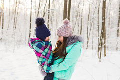 Happy family mother and baby girl daughter playing and laughing in winter outdoors in the snow Stock Images
