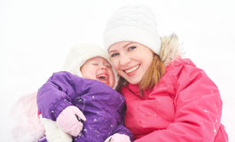 Happy family mother and baby girl daughter playing and laughing in winter snow Royalty Free Stock Image