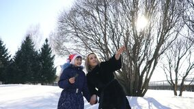 Happy family mother and baby girl daughter run, walk playing in winter outdoors in the snow stock video footage