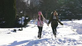 Happy family mother and baby girl daughter run, walk playing in winter outdoors in the snow stock video