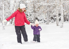 Happy family mother and baby girl daughter run, walk and playing in winter snow Stock Photo