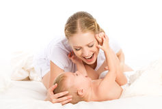 Happy family mother and baby having fun playing, laughing on bed Royalty Free Stock Photography
