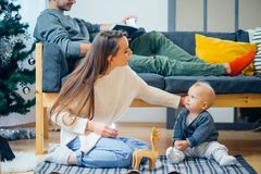 Happy family mother and baby little son playing home on Christmas holidays Stock Photos