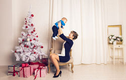 Happy family mother and baby little son playing home on Christmas holidays. New Year`s holidays. Toddler with mom in the Royalty Free Stock Photos