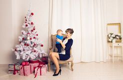 Happy family mother and baby little son playing home on Christmas holidays. New Year`s holidays. Toddler with mom in the Stock Images