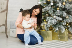 Happy family mother and baby little son playing home on Christmas holidays. New Year`s holidays. Toddler with mom in the. Festively decorated room with Royalty Free Stock Image