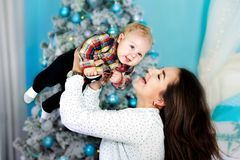Happy family mother and baby little son playing home on Christmas holidays. New Year`s holidays. Toddler with mom in the stock image