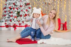 Happy family mother and baby little son playing home on Christmas holidays.Toddler with mom in the festively decorated room with C. Hristmas tree. Portrait of Royalty Free Stock Photo