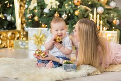Happy family mother and baby little son playing home on Christmas holidays.Toddler with mom in the festively decorated room with C. Hristmas tree. Portrait of Stock Images