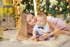 Happy family mother and baby little son playing home on Christmas holidays.Toddler with mom in the festively decorated room with C. Hristmas tree. Portrait of Stock Photo
