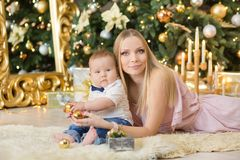 Happy family mother and baby little son playing home on Christmas holidays.Toddler with mom in the festively decorated room with C. Hristmas tree. Portrait of Royalty Free Stock Photos