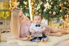 Happy family mother and baby little son playing home on Christmas holidays.Toddler with mom in the festively decorated room with C. Hristmas tree. Portrait of Royalty Free Stock Image