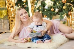 Happy family mother and baby little son playing home on Christmas holidays.Toddler with mom in the festively decorated room with C. Hristmas tree. Portrait of Royalty Free Stock Images