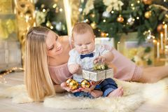 Happy family mother and baby little son playing home on Christmas holidays.Toddler with mom in the festively decorated room with C. Hristmas tree. Portrait of Stock Photos