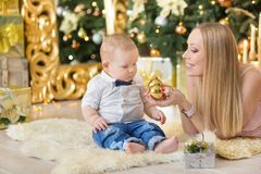 Happy family mother and baby little son playing home on Christmas holidays.Toddler with mom in the festively decorated room with C. Hristmas tree. Portrait of Stock Image