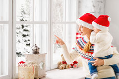 happy family mother and baby look out window for the winter Christmas royalty free stock image