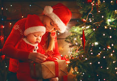 Happy family mother and baby near Christmas tree in holiday nigh Stock Photo
