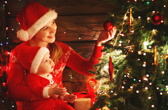 Happy family mother and baby near Christmas tree in holiday nigh Royalty Free Stock Images