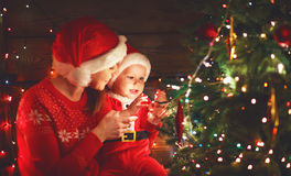 Happy family mother and baby near Christmas tree in holiday nigh Stock Image