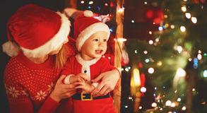 Happy family mother and baby near Christmas tree in holiday nigh Stock Photography
