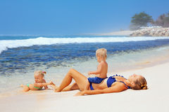 Happy family - mother, baby son, daughter sunbathing on sea beach Royalty Free Stock Photos