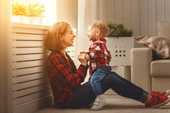 Happy family mother and baby son hugging, playing and laughing. At home stock photography