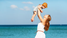 Happy family mother with baby son walks by ocean on beach in sum Stock Images