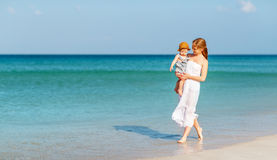 Happy family mother with baby son walks by ocean on beach in sum Stock Photography