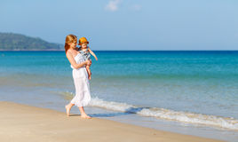 Happy family mother with baby son walks by ocean on beach in sum Royalty Free Stock Image