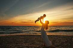 Happy family mother with baby son walks by ocean on beach in sum Stock Photos