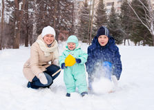 Happy family mother and baby and teenager in winter park Stock Images