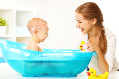 Happy family mother bathes the baby in  bath Stock Photos