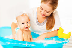 Happy family mother bathes the baby in bath. Happy family mother bathes the baby in a blue bath stock photos