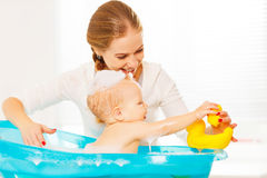 Happy family mother bathes the baby in bath. Happy family mother bathes the baby in a blue bath royalty free stock image