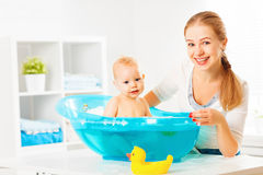 Happy family mother bathes the baby in bath. Happy family mother bathes the baby in a blue bath stock images