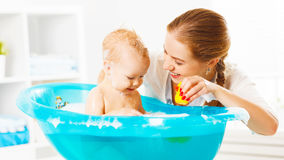 Happy family mother bathes the baby in bath. Happy family mother bathes the baby in a blue bath royalty free stock photo