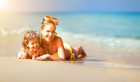 Happy family mother and chid daughter in masks on beach in summe Stock Photos