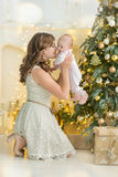 Happy family mother and child baby boy on Christmas morning at the tree with gifts, home decoration, interior house Stock Photos