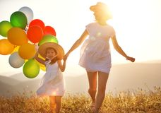 Happy family mother and child with balloons at sunset in summer Royalty Free Stock Photography